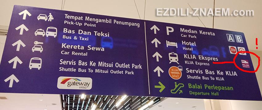 Фиолетовые указатели на поезда KLIA Transit в аэропорту Куала Лумпур