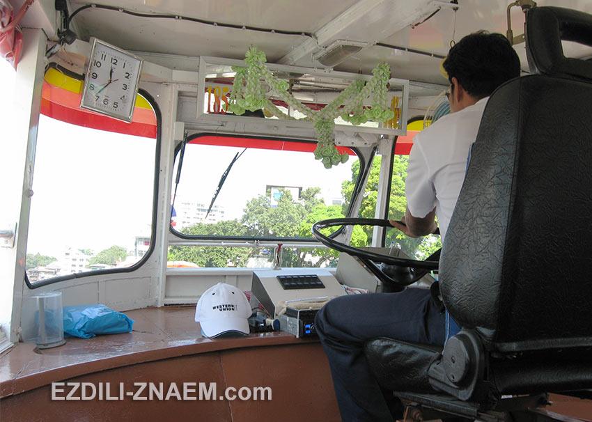 Капитан речного трамвая на реке в Бангкоке