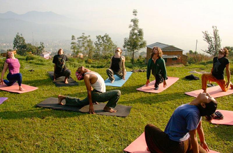 группа туристов занимается йогой в Непале