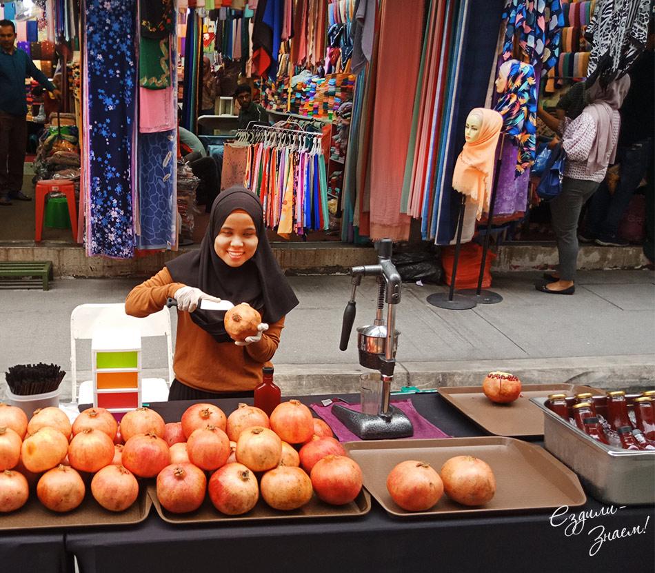 Девушка продает свежевыжатый гранатовый сок
