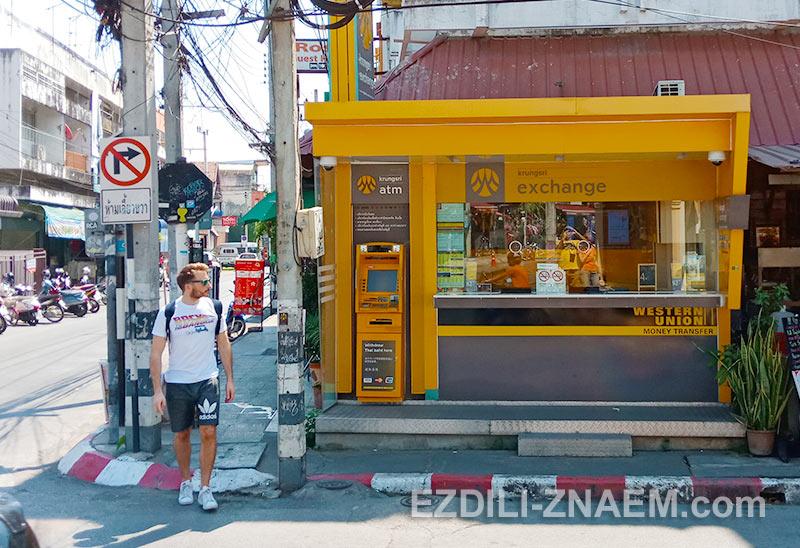 Турист рядом с банкоматом и обменным пунктом в Таиланде