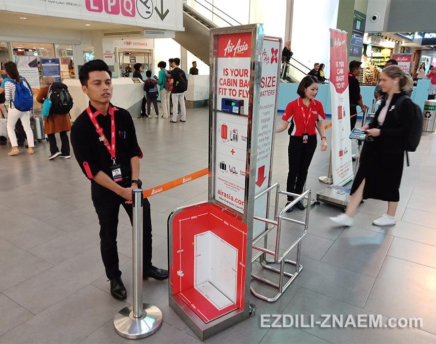 Сотрудники AirAsia теперь строго замеряют и взвешивают ручную кладь в аэропорту KLIA2 в Куала Лумпур
