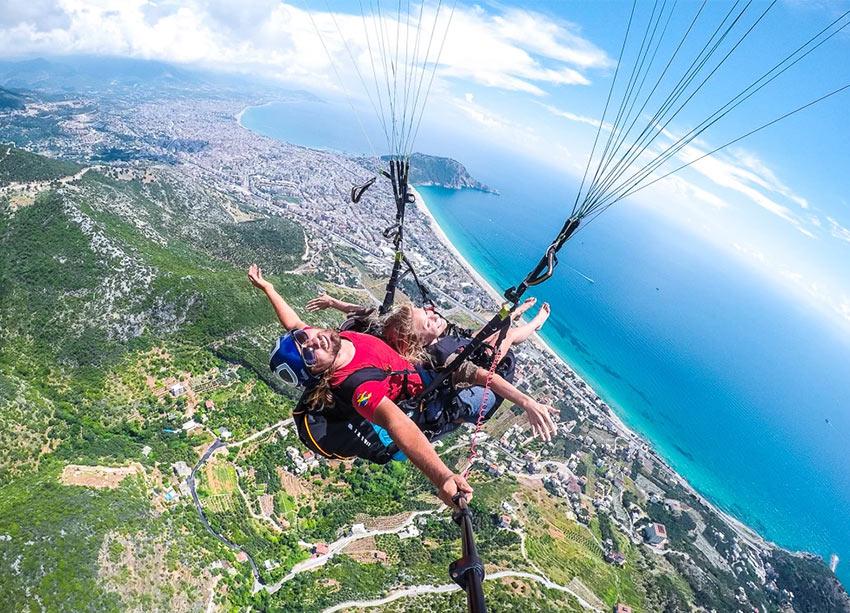 Туристы летают на параплане в Алании